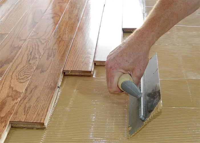 Hardwood flooring installation laying on glue